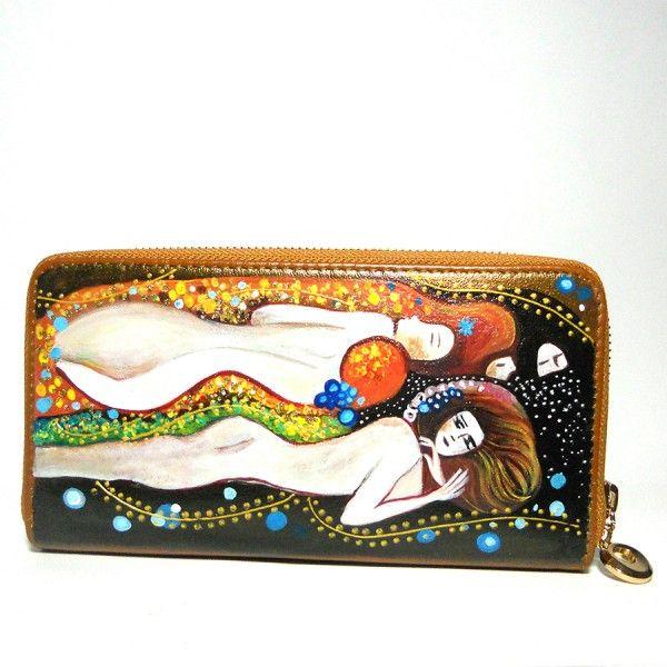 Portafoglio in pelle dipinto a mano Serpenti D'Acqua Klimt  95.00€  Portafogli in pelle dipinto a mano, SERPENTI D'ACQUA, un dipinto ricco di dettagli del grande Gustave Klimt su portafogli in pelle cognac. Il dipinto presenta anche rilievi in glitter oro. Misure 20×10