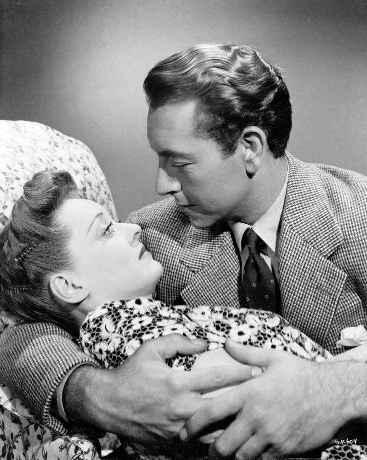 Medium shot of Bette Davis as Charlotte Vale being embraced by Paul Henreid as Jerry Durrance.