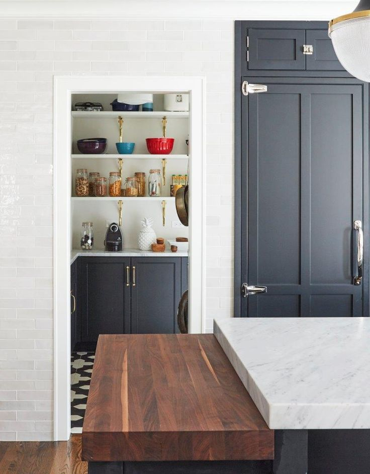 White glazed linear backsplash tiles frame the doorway of a pantry fitted  with black and while pantry floor tiles accenting dark gray shaker cabinets  fitted ...
