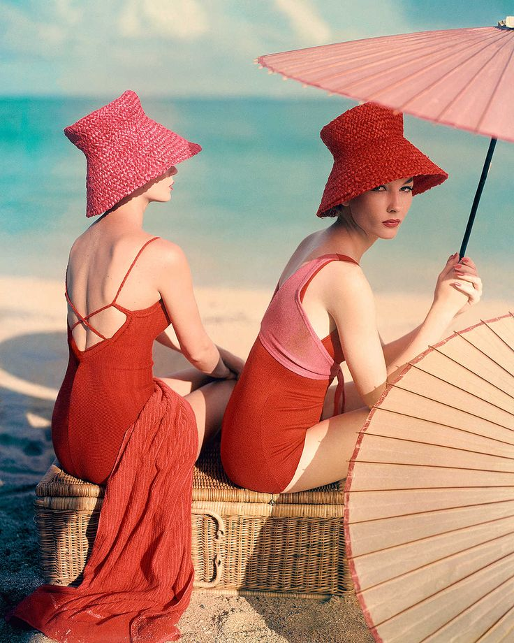 """Two models lounge stylishly on a beach in """"Red Parasol"""" by Louise Dahl-Wolfe. They sit on a wicker basket, wearing red bathing suits—one with crisscross straps, the other with a shock of pink running from back to front. Salmon-pink parasols and fuchsia straw hats support the color scheme. The photography was published in Vogue in January 1963."""