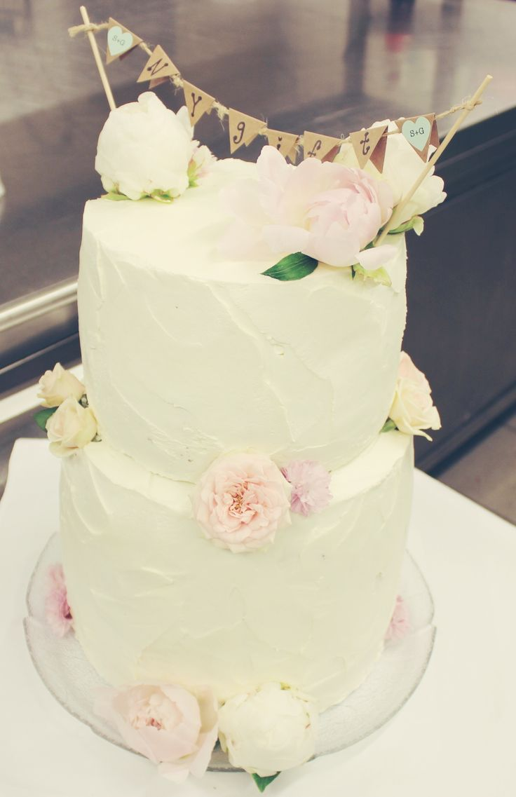 """white wedding cake with cute """"just married"""" banner."""