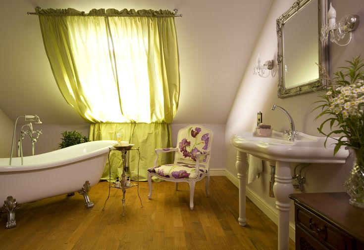violet pastel stylish bathroom with feestanding clawfoot bathtub and armchair in fabric flowers