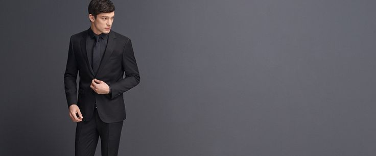 Grey slim fit suit over a grey dress shirt and grey tie.