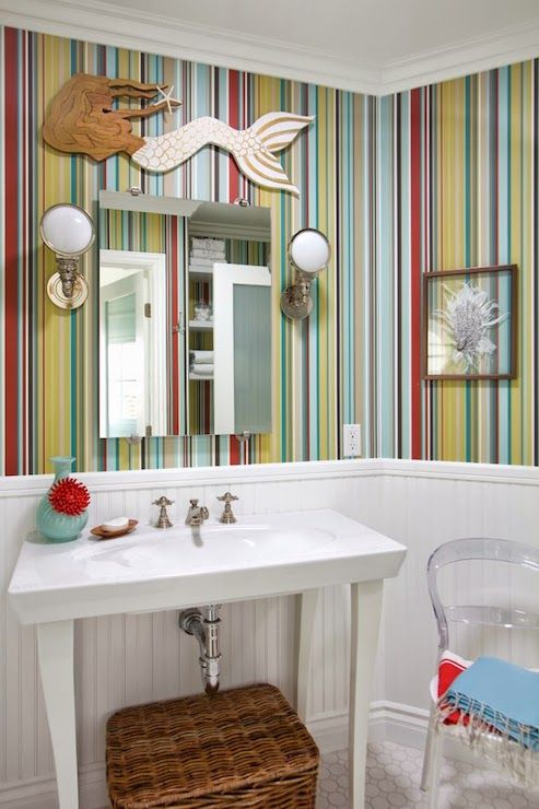 Fun, coastal bathroom with beadboard paneled lower wall alongside upper wall finished in multi-colored striped wallpaper which highlights a carved wooden mermaid mounted above the frameless vanity mirror flanked by nautical wall sconces over a contemporary washstand sink.