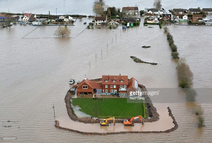Worker's continue to build flood defences around Moorland resident Sam Notaro's house in the flooded village of Moorland near Bridgwater on the Somerset Levels on February 10, 2014 in Somerset, England. Thousands of acres of the Somerset Levels have been under water for weeks, yet flood levels are still rising and worryingly, more rain is forecast for later this week.