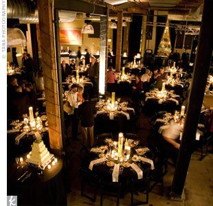 Black tablecloths and stark white napkins created an elegant look for the reception, while candlelight brought warmth to the industrial space.