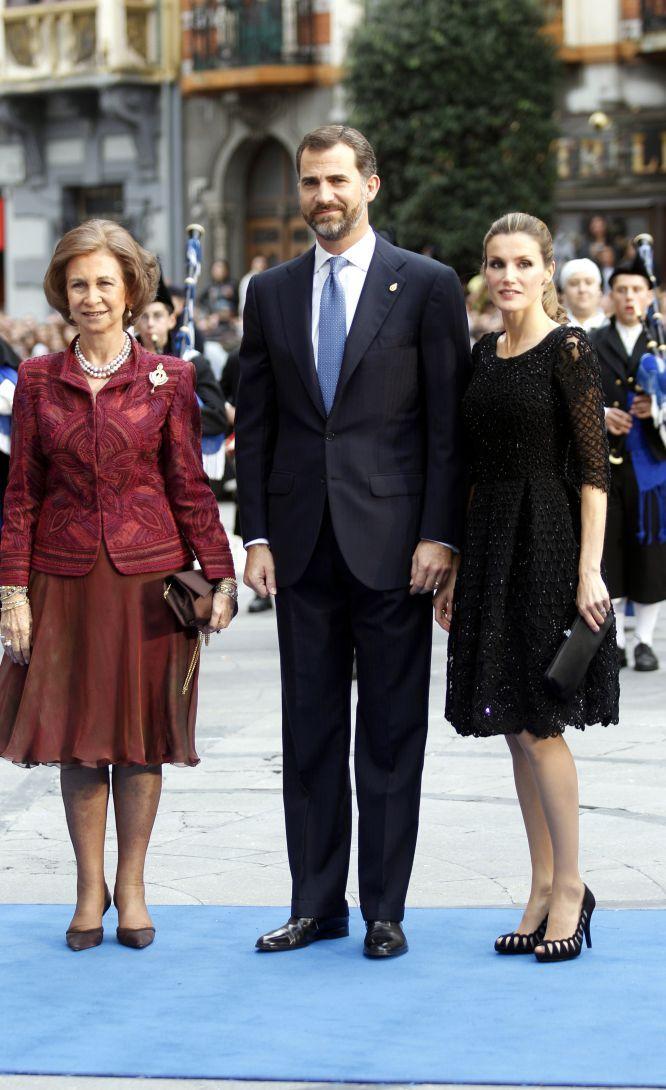 En la edición de 2010 de los premios Príncipe de Asturias, doña Letizia apostó de nuevo por el color negro con toques brillantes en su traje, y llevó el pelo recogido en una coleta. En la foto, con don Felipe y doña Sofía.