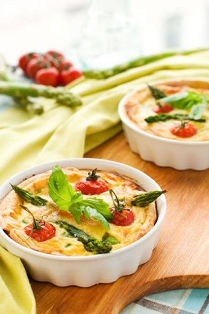 """This tempting tomato and asparagus quiche recipe can be made in a nine inch pan or a pair of smaller ones. You can add a cup of diced cooked chicken or ham when mixing the egg mixture if you have some to use up, although that is optional. Some crispy bacon would also give this a """"Quiche Lorraine"""" feel, but it is up to you; perhaps you would prefer to keep this vegetarian."""