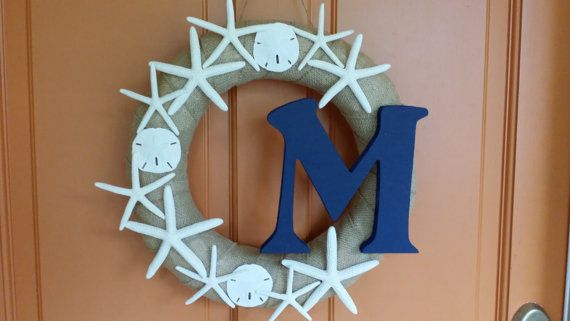 Bring the beach to your home. Handmade 15 wreath is wrapped in burlap with sand dollars and starfish and personalized with the letter of your