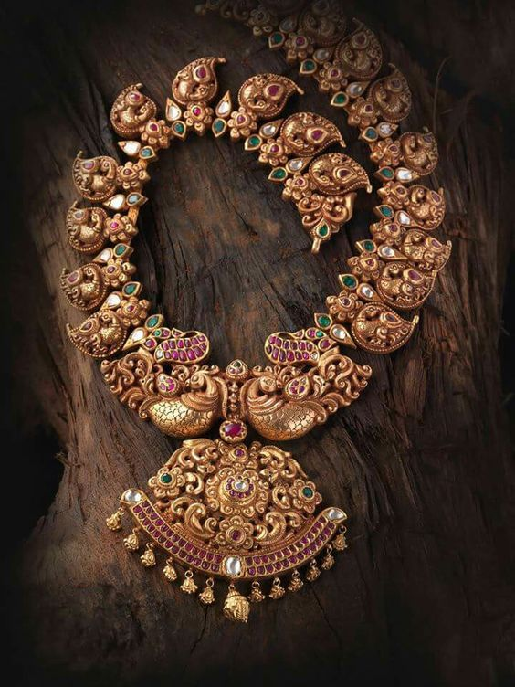 This stunning peacock motif necklace is intricately designed with rubies and emeralds embedded in the design itself. Perfect for your temple jewelry collection. | Photo Source: aprabhugaonkar | Every Indian bride's Fav. Wedding E-magazine to read. Here for any marriage advice you need |www.wittyvows.comshares things no one tells brides, covers real weddings, ideas, inspirations, design trends and the right vendors, candid photographers etc.