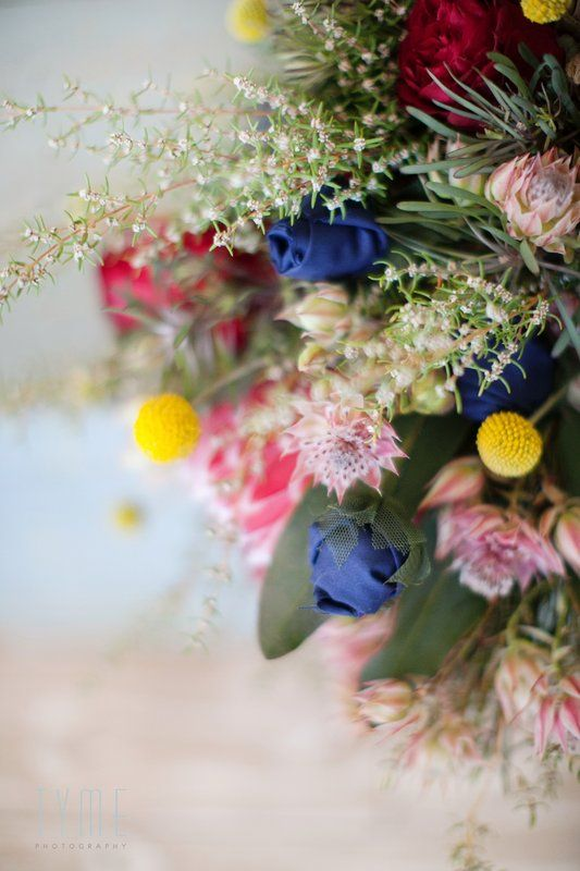 Beautiful winter wedding bouquet by Eco-Chic Weddings. Fynbos, proteas, handmade flowers, navy blue and burgundy and beautiful hessian texture! Photo By Tyme Photography
