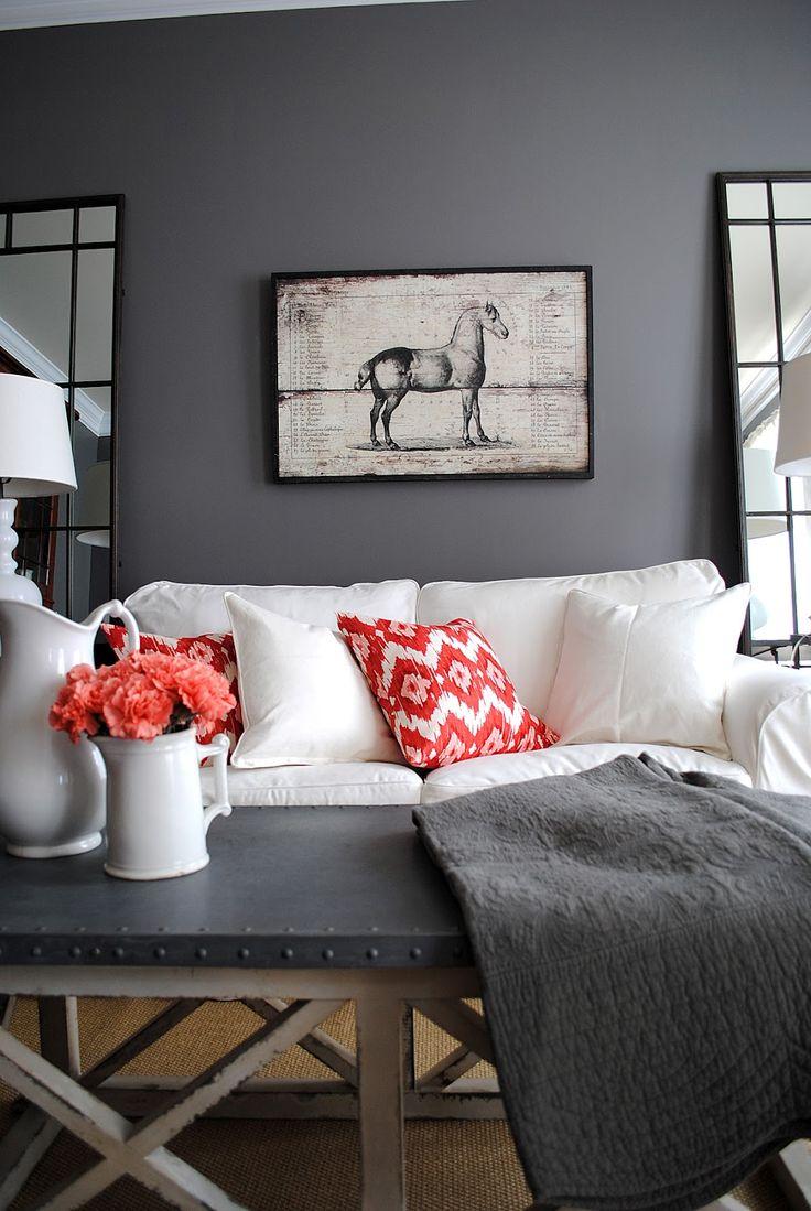 Красные подушки украшают интерьер в серой гамме.
