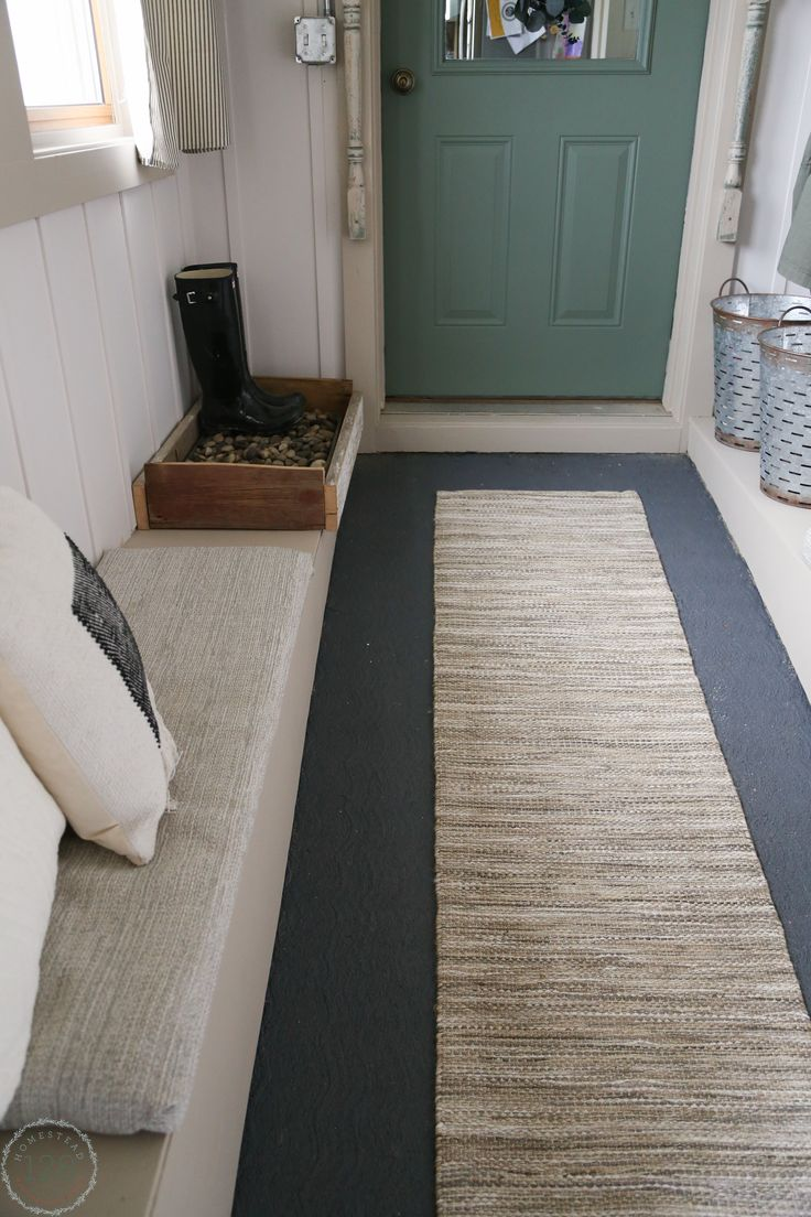 Gray painted cement flooring, upholstered benches, and shoe storage in the  farmhouse mudroom with