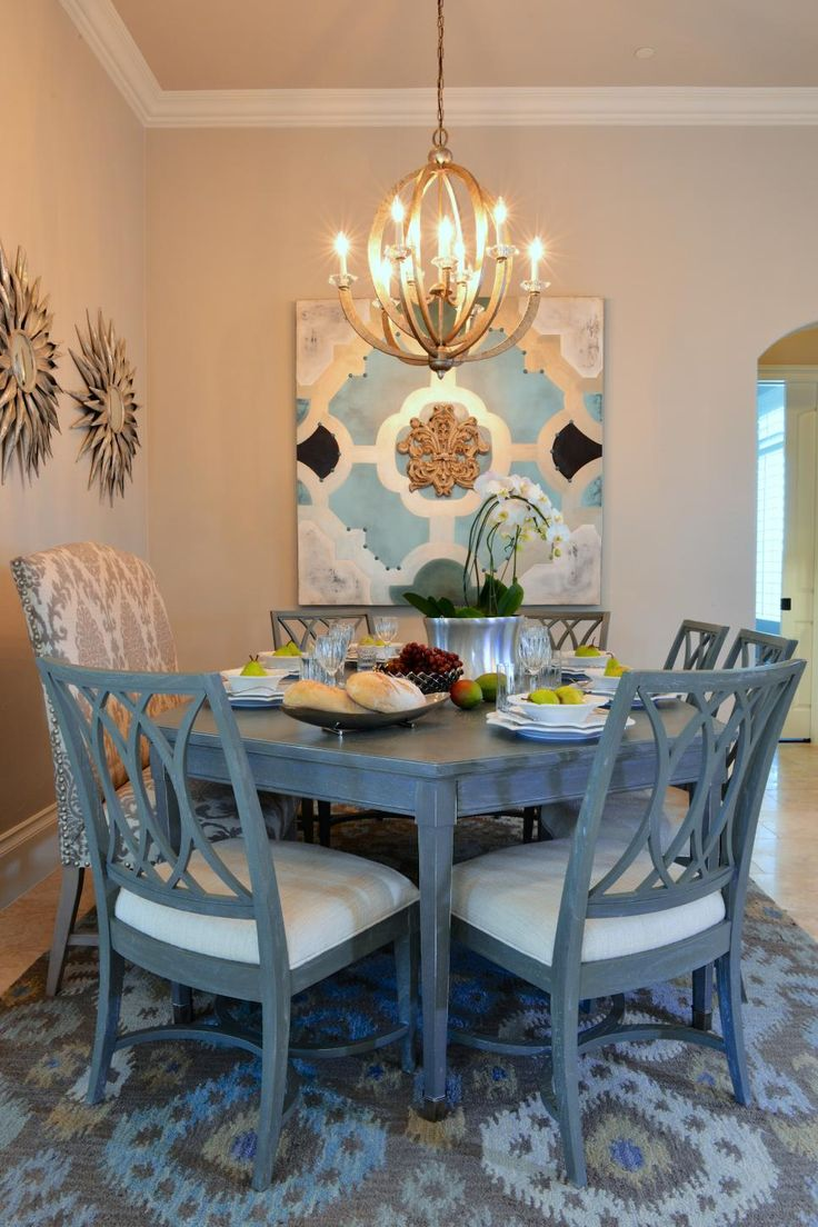 The chic artwork and ikat area rug draw color inspiration from the distressed dining table and chairs. Paired with the soft beige walls, the dusty blue hue is an elegant accent color.