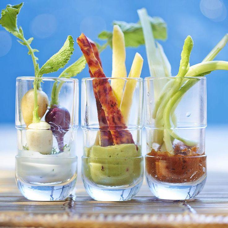 Mélanger le fromage avec la ciboulette hachée, 1 pincée de sel et le curcuma. Mixer la pulpe d'avocat avec l'oignon coupé en morceaux, le jus de citron et le piment jusqu'à l'obtention d'une crème fine. Mixer les tomates séchées avec le jus de tomate et l'anchoïade. Répartir toutes ces sauces dans différents petits verres et garder au frais. Préparer les légumes : les peler, laver et découper, et les servir accompagnés des sauces.