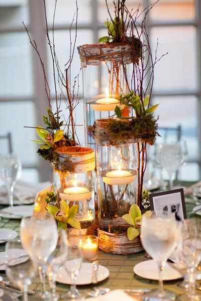 Tall cylindrical glasses with floating candle creating a rustic style some twigs with daisies and sunflowers..mums