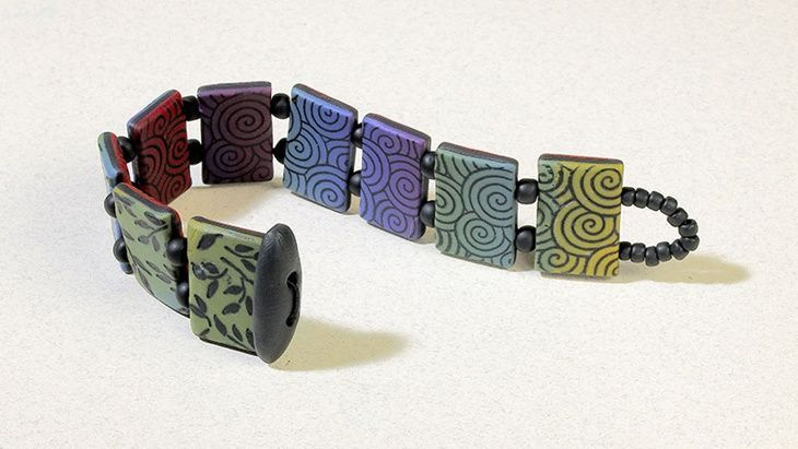 Reversible rainbow bracelet make a four-color Skinner blend, and then add detail with rubber stamps and ink for a refined bracelet. Polymer clay. Rubber stamping.