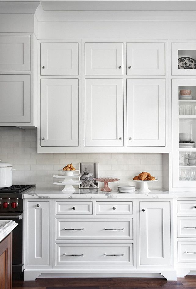 Tall cabinetry, soffit, subway tiles, built in hood over cooktop - has a french kitchen feel