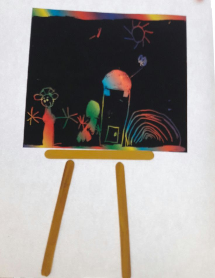 """Schildersdoek gemaakt door een """"krastekening""""  te maken met een kraspen. De krasblokken zijn te koop bij de Action in regenboogkleuren en zilver. Daaronder een schildersezel geplakt  m.b.v. gekleurde ijslolly stokjes."""