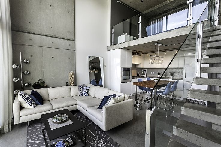 Plush couch in white in the living area with a exposed concrete wall Classy Customized Penthouse In Vancouver Offers A Relaxed Urban Retreat