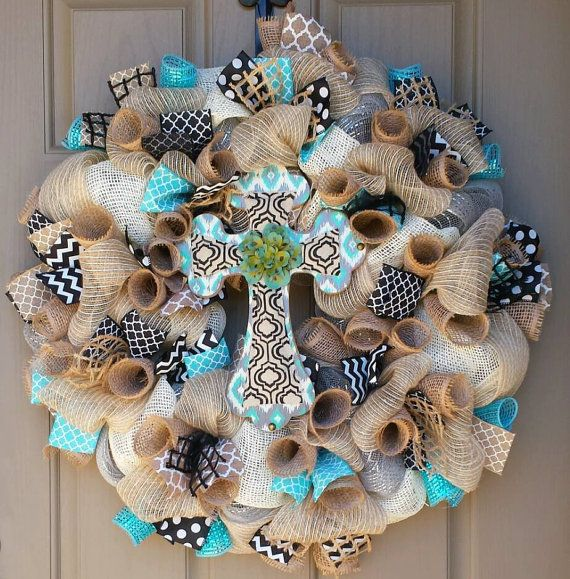 Beautfiful cross wreath blending burlap, aqua, black and cream into a fabulous decorative piece for your front door or mantle! The wreath is made with a wired work wreath form, burlap, deluxe matte and metallic deco mesh, deco mesh ribbon, and wired ribbon. Due to ribbon availability,