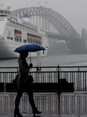 A Sydney resident shelters under an umbrella as early morning rain falls while walking along Circular Quay on Sydney Harbour on January 29, 2013.