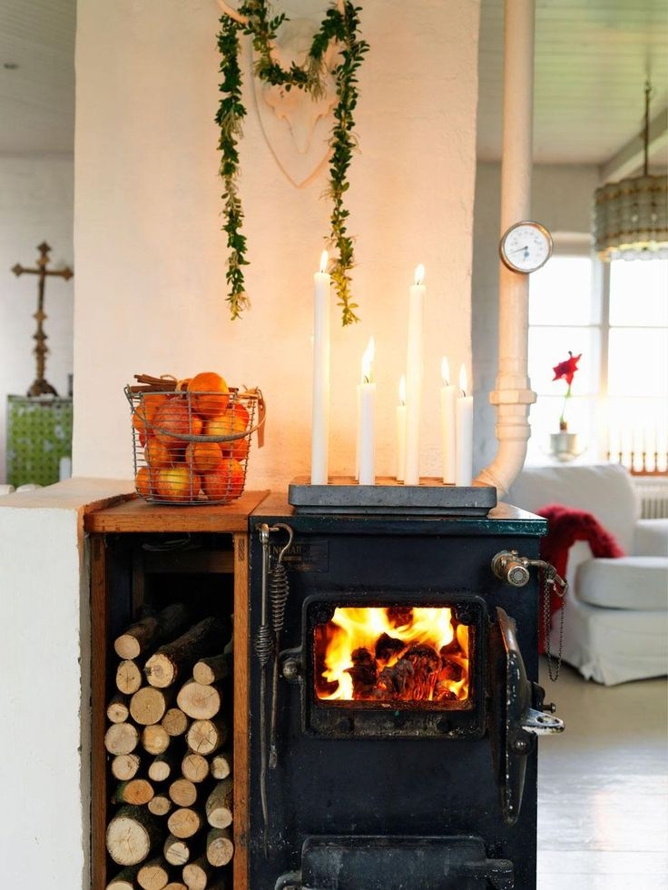 Vedpannan i köket brinner välkomnade och ofta. På skorstensstocken hänger vitmålade hjorthorn, fyndade på loppis. Buxbomsgirlangen har Lotta gjort av ståltråd. Platsbyggd vedförvaring i ek, Starfelts Snickeri. Stumpastake, Olsson & Gerthel.