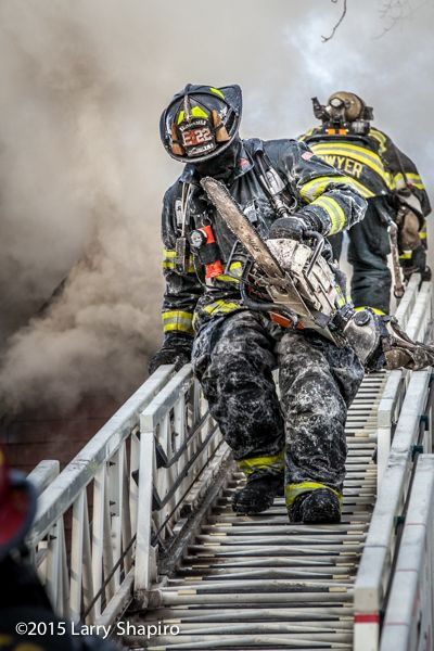 fireman on later with saw covered in ice