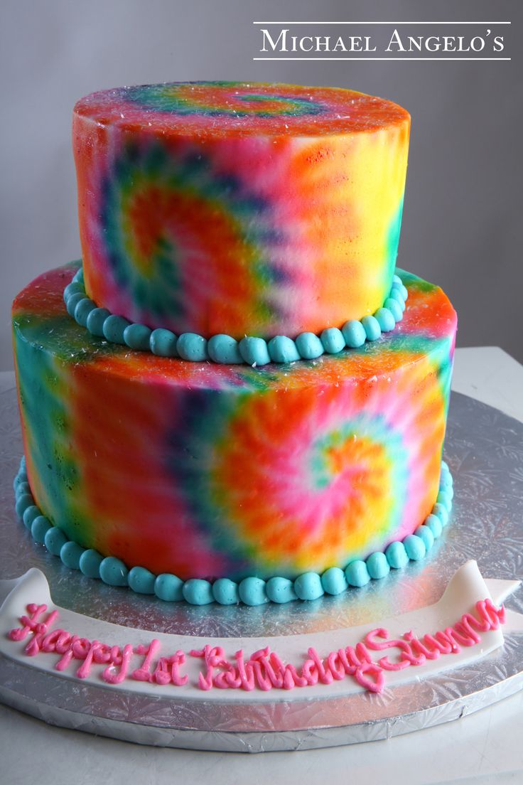 Tie Dye Surprise #32Milestones  This is a two-tier round cake. It is iced in tie dye buttercream and trimmed with a aqua beaded border. A matching smash cake is also featured.