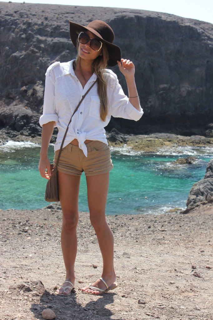 big floppy brown hat, white button up shirt tied over beige shorts
