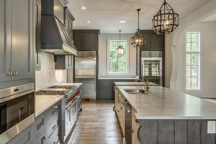Mediterranean kitchen features gray shaker cabinets adorned with brass hardware paired with grey ...