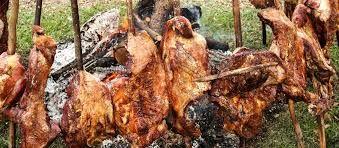 Cuando la carne empiece a desprender líquido se le rocía cerveza. Finalmente se retira y se pica en trozos sobre una mesa cubierta de hojas de plátano