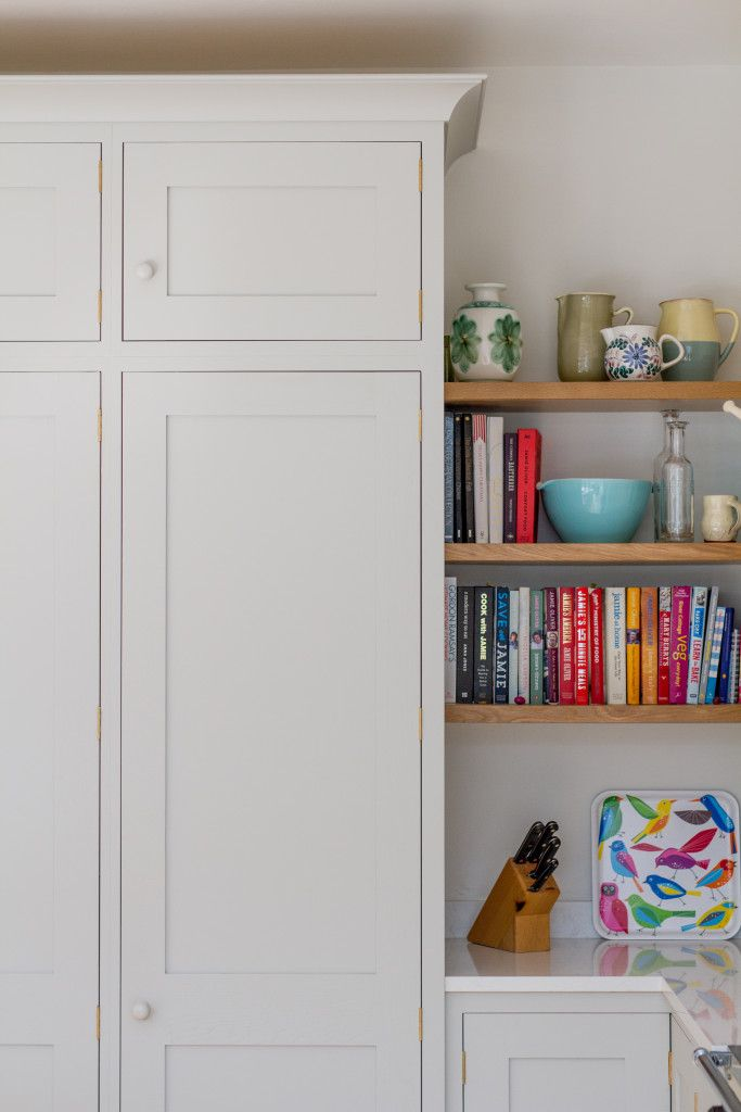 Sustainable Kitchens - The Scandinavian Woodland Inspired Kitchen. Tall shaker style oak larder cabinet painted in Farrow & Ball Pavilion Gray. Next to the larder are three floating oak shelves lined with cookbooks and ceramics. The Bianco Venato engineered quartz worktop is also visible.
