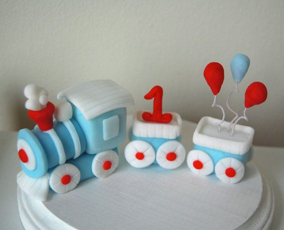 Make this adorable trains next trip to the top of your cake! This train is made with modeling fondant and comes with a number and balloons.  This set would be the perfect size for an 8 inch cake.  Order as is, or customize it and choose your own colors, number, and balloons! If you want other items placed in the carriages let us know! We would love to make it even more personalized.  *Prices may vary depending on amount of customization*  Some colors are prone to fading if your item is made…