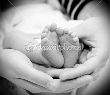 Small feet baby holds his mother in her hands by AntonioGravante - Foto Stock