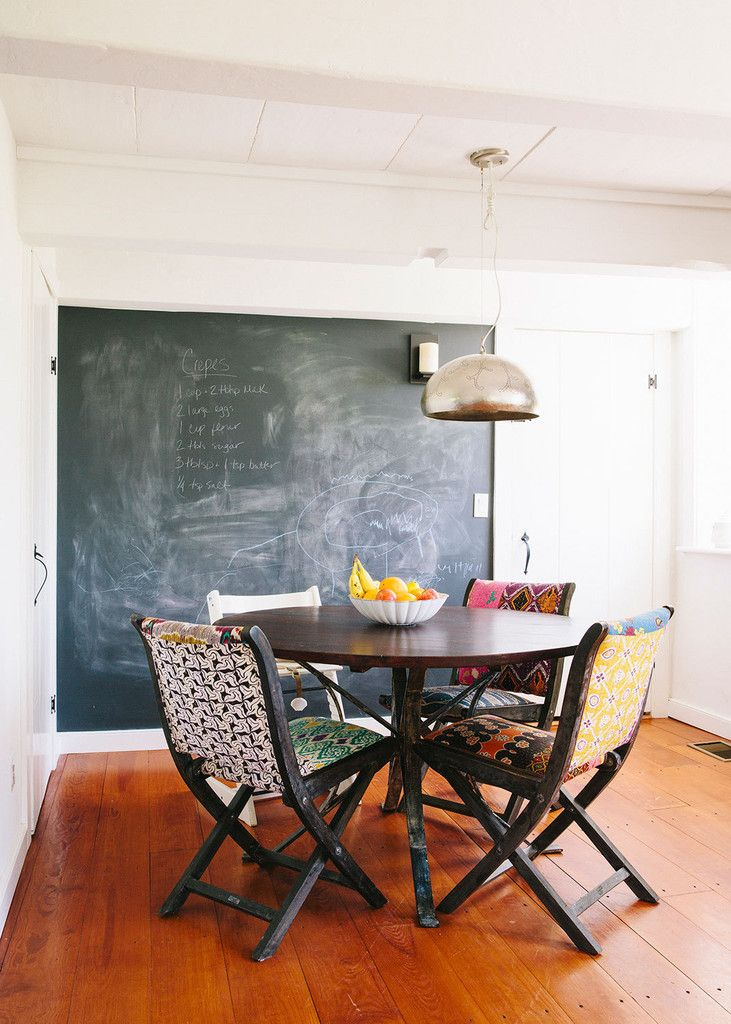 A chalkboard wall behind the dining table keeps little ones busy for hours.  Click through for the full tour of this kid-friendly country cottage! | Lonny.com