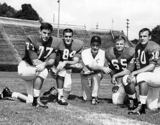 University of Georgia Bulldogs head football coach Johnny Griffith poses with players on a football field. Photo reverse reads: L-R: Atlanta boys with Coach Griffith. Paul Holmes, RT, Northside; Mickey Babb, RE, Brown; Coach Griffith, former old Boys High star; Terry Scott, LE, Brown; Larry Rakestraw, QB, West Fulton. M004_2385, WSB Radio Records, Popular Music and Culture Collection, Special Collections and Archives, Georgia State University Library.