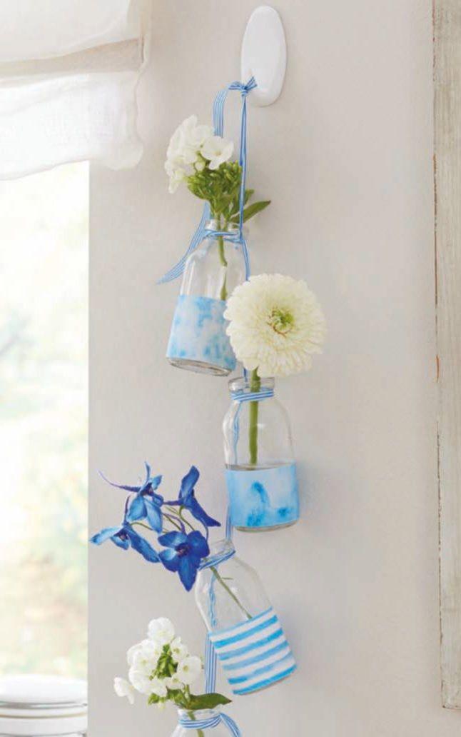 Preziose bottiglie di vetro: come riciclarle   Niente di meglio dei fiori per portare una ventata di freschezza ed allegria alla casa. Se ad accoglierli èuna cascata di bottigliette riciclate tanto meglio. Si appendono al muro aumentandone leffetto decorativo. Questi vasi sospesi sono perfetti per accogliere anche i più semplici fiori di campo. Ecco come realizzarli.  Materiale occorrente Piccole bottiglie di vetro (ideali quelle dei succhi di frutta) Carta decorata Righello forbici cutter e…