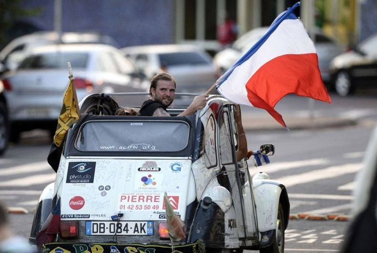 A French supporter holds a French flag in a car at the Ribeirao Preto airport as the French team players fly to Rio de Janeiro