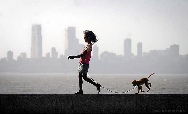Девочка со своей ручной обезьянкой на набережной в Мумбаи.