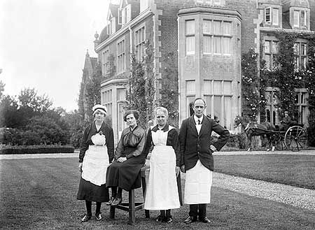 In this Edwardian scene, the four 'heads of department' pose on the lawn in front of Grendon Hall. The housekeeper, seated, ran the establishment. She was assisted by the cook who managed the kitchen and the head housemaid who managed the cleaning staff. The butler was in charge of his own specialist sphere. The coachman is in the background.