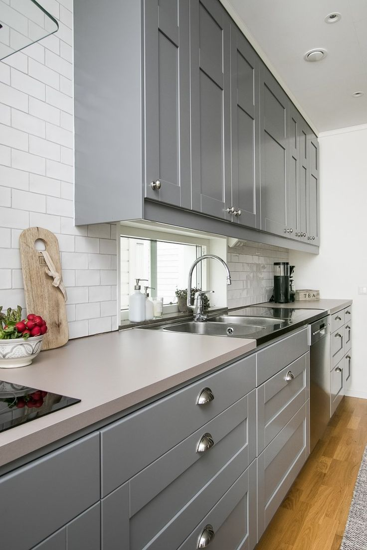 Ett grått kök med snygga knoppar på överskåpen och praktiska skålformade handtag på bänkskåpen | Ballingslöv