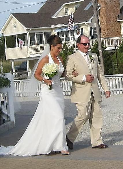Walking In With Dad Wearing An Ivory Suit For A Beach Wedding