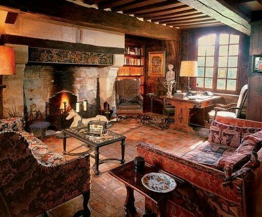 Cozy old english and old world styled sitting room with oversized fireplace, tapestry furniture and wood beams