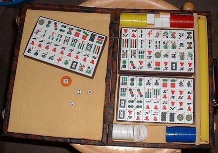 Länsimainen pelisalkku sisältöineen. Mahjong-tiilten lisäksi neljä valkoista varatiiltä, erivärisiä pelimerkkejä, noppapari ja tuuliosoitin pidikkeineen.