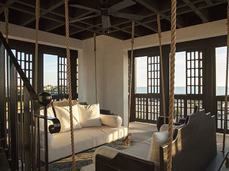 Mediterranean lounge features hanging sofas suspended from ropes facing each other atop gray Moroccan rug surrounded by sliding lattice doors leading to balcony.