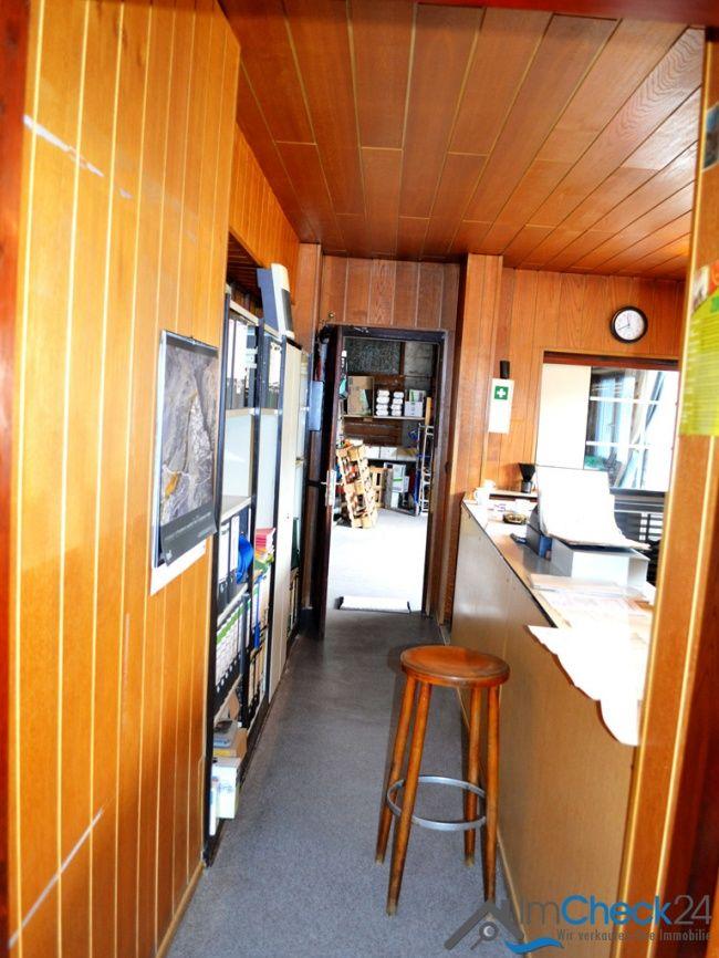 Hauptbüro mit Holzdielen und Teppichboden.