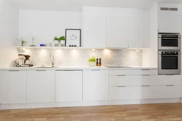 Kök med vita luckor och stilrena handtag. Stänkskyddet ovanför den ljusa bänkskivan med underlimmad diskho är i ljus carraramarmor | Ballingslöv