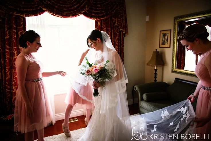 Bride in her Enzoani gown getting pampered by her pink dressed bridesmaids.