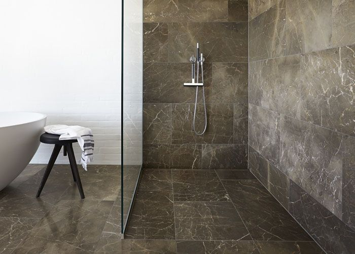 Beautiful and elegant glass shower screen in a shower with linear floor drain with a floor tile that matches the rest of the bathroom floor. unidrain®: GlassLine & HighLine